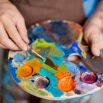 Hand of painter mixing paints